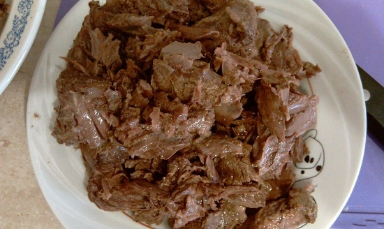 Отварное мясо отделяем от кости и режем