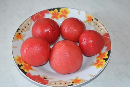 аккуратно достаем томаты и снимаем с них кожицу