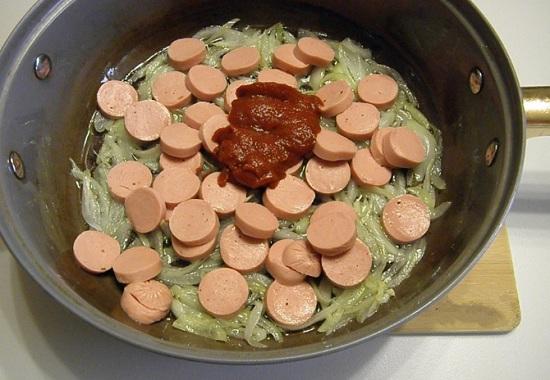 Выложим к луку в сковороду сосиски и пасту томатную
