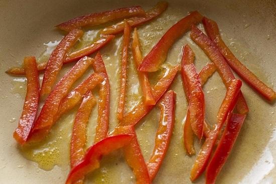 Выкладываем нашинкованный перец и обжариваем