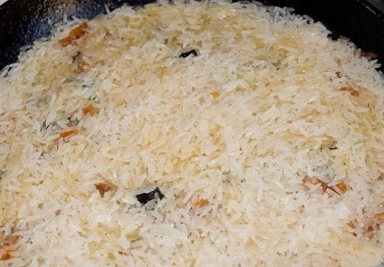Выложим рис в сковороду поверх моркови с сухофруктами