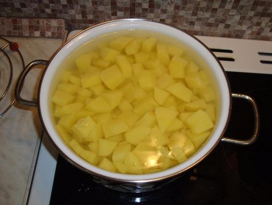 Выкладываем измельченный картофель в кастрюлю
