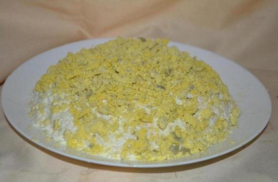 Измельчаем желтки и посыпаем ими салат